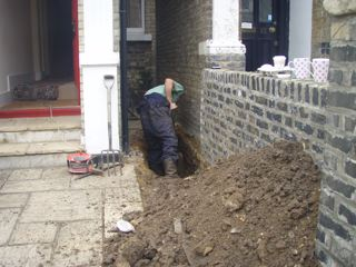 Engineers carrying out repairs and removal of soil to take pictures to provide fro insurance company evidence