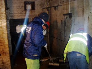 Lower basement area being washed down into large sump to allow pumps to remove the last amount of water