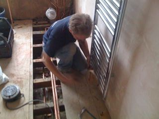 Engineer installing towel rail in the bathroom area