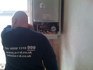 Engineer installing new boiler, prior to drilling out the flue on the outside wall